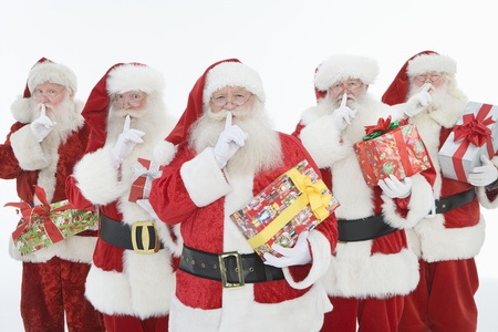 lined up: Group of men dressed as Santa Claus holding gifts LANG_EVOIMAGES