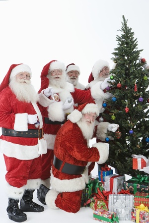 decorating christmas tree: Group of men dressed as Santa Claus decorating Christmas tree LANG_EVOIMAGES