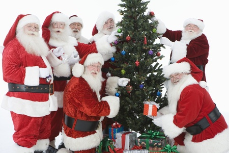 Group of men dressed as Santa Claus decorating Christmas tree Stock Photo