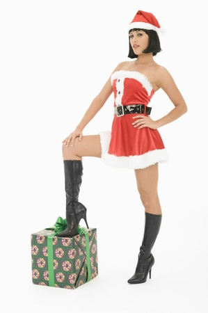 sexy christmas elf: Mrs Claus standing with one foot on gift LANG_EVOIMAGES