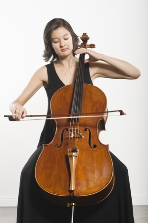 cellist: Mixed race cellist sits playing