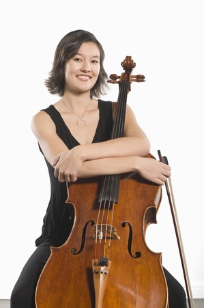 Female cellist sits with arms folded across cello Stock Photo - 12735137