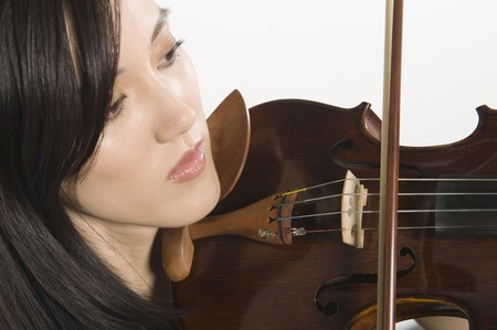 Young Asian woman concentrates on playing the violin Stock Photo - 12735175