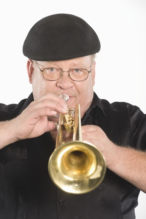 flat cap: Mature man in flat cap playing the trumpet