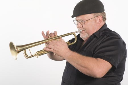 Mature man in flat cap playing the trumpet Stock Photo - 12735200