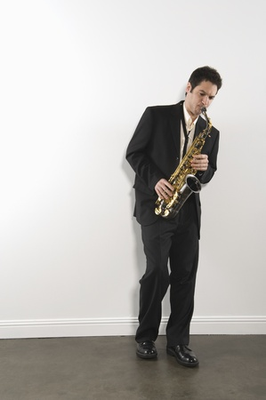 Mid adult man stands in suit playing the saxophone Stock Photo - 12735203