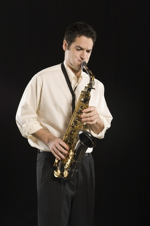 Mid adult man stands in shirt playing the saxophone Stock Photo - 12735195