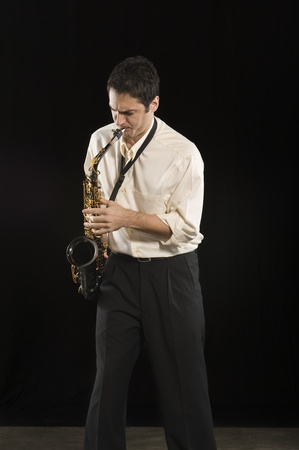 Mid adult man stands in shirt playing the saxophone Stock Photo - 12735189