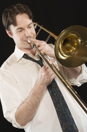 Mid-adult man with open-collar shirt plays the trombone Stock Photo - 12735199