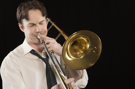 Mid-adult man with open-collar shirt plays the trombone Stock Photo - 12735196