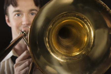 Mid-adult man with open-collar shirt plays the trombone Stock Photo - 12735197