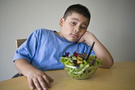 preteen boy: Pre-teen (10-12) boy sitting at desk with salad LANG_EVOIMAGES