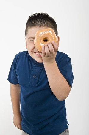 Pre-teen (10-12) boy holding doughnut over eye Stock Photo - 12735183