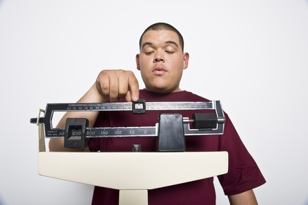 Teenage (16-17) boy using weight scales Stock Photo - 12735252