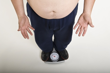 body concern: Low section of man standing on bathroom scale