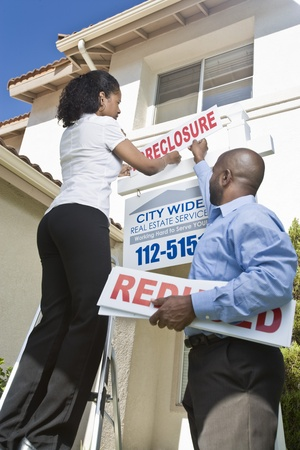 Two people putting up notice outside house Stock Photo - 12735207