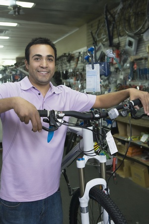 Bike shop assistant stands holding new bike Stock Photo - 12735246