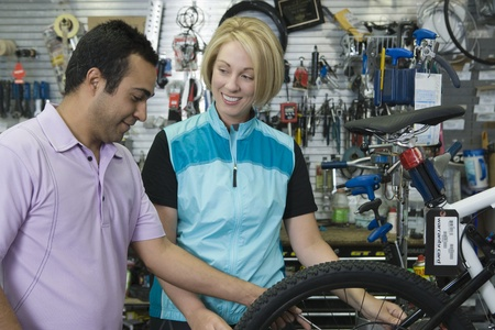 Bike shop assistant helps female cyclist Stock Photo - 12735249