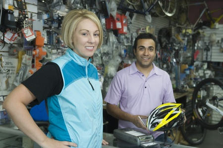 Female cyclist buying helmet at bike shop cash desk Stock Photo - 12735542
