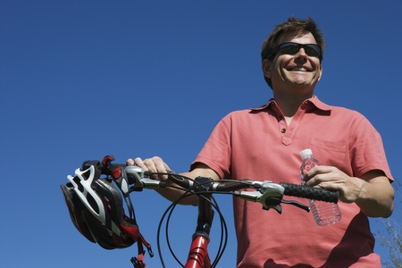 Mature man stands holding bicycle handlebars Stock Photo - 12735254