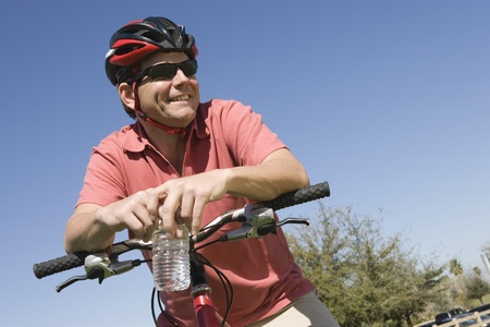 Mature man in cycling helmet leans on bicycle handlebars Stock Photo - 12735523