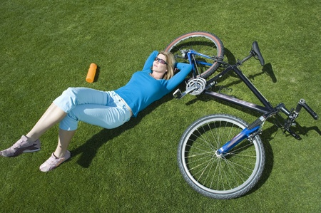 Female cylcist lying on grass  with her bike Stock Photo - 12735295