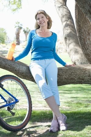 capri pants: Mature woman leans on tree with her bike LANG_EVOIMAGES