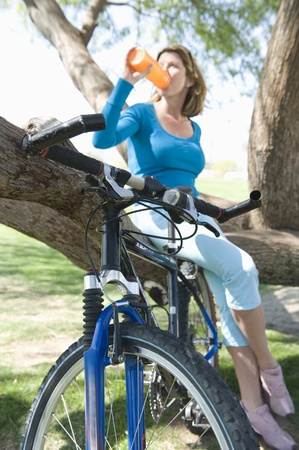 capri pants: Mature woman drinking water on a tree with her bike