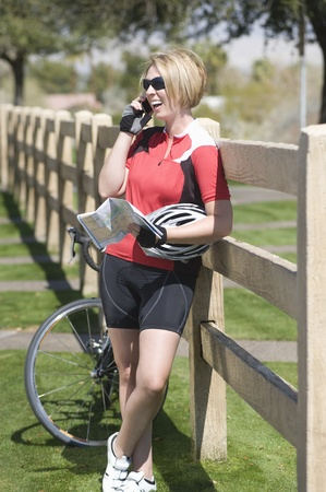 Cyclist leans on fence talking on phone with her bike Stock Photo - 12735284