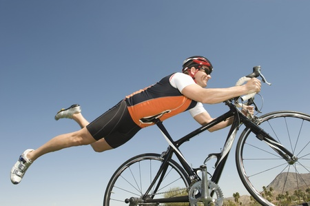 horseplay: Male cyclist balances his stomach on bicycle seat