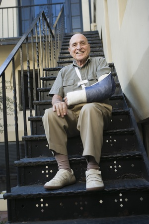 Man with broken arm sitting on stairs Stock Photo - 12735306