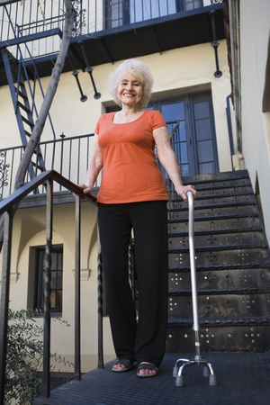 Woman with walking cane outside house Stock Photo - 12735307