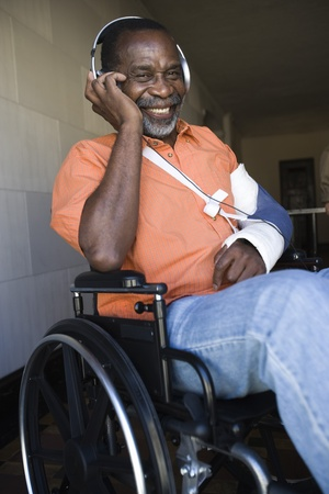 the ageing process: Elderly man in wheelchair listening to music LANG_EVOIMAGES