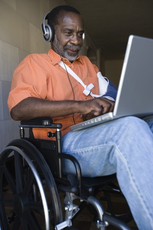 the ageing process: Elderly man in wheelchair listening to music and using laptop