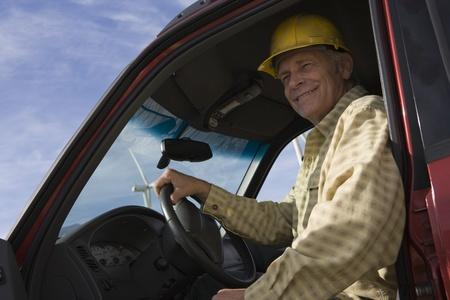 wind farm: Senior hombre en un cami�n en el parque e�lico