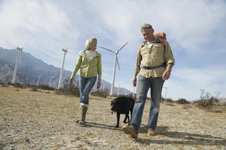 casual hooded top: Senior pareja paseando con perro cerca de parque e�lico LANG_EVOIMAGES