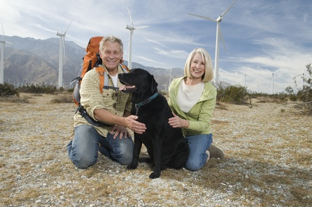 casual hooded top: Senior couple with dog near wind farm
