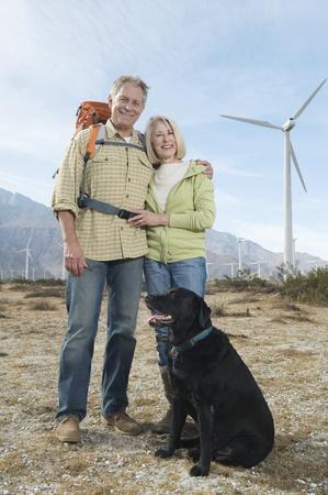 casual hooded top: Senior couple with dog near wind farm