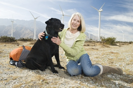 casual hooded top: Senior woman with dog near wind farm