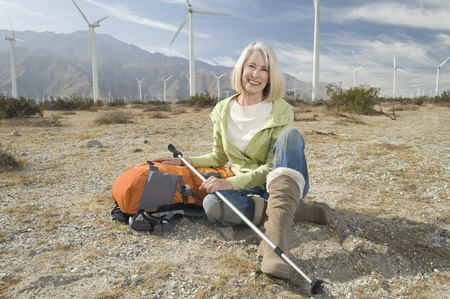 casual hooded top: Senior woman with backpack near wind farm