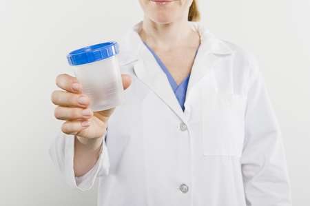Doctor with sample pot mid section Stock Photo - 12737894