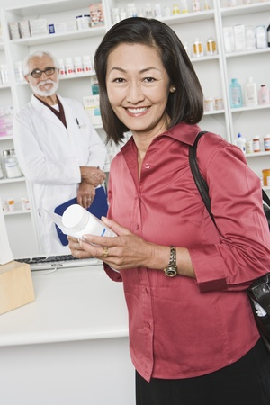 Woman picking up prescription drugs at pharmacy Stock Photo - 12737962