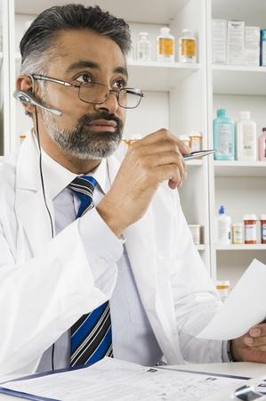 Male pharmactist working in pharmacy Stock Photo - 12737981