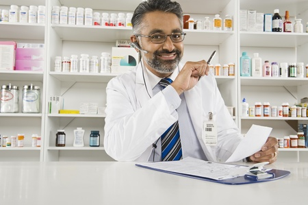 greying: Male pharmactist working in pharmacy