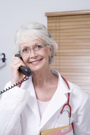 Senior healthcare professional holds telephone receiver Stock Photo - 12738027