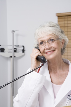 Senior healthcare professional holds telephone receiver Stock Photo - 12738028