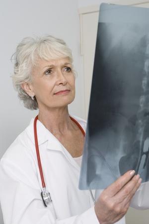Senior medical practitioner examines xray Stock Photo - 12738030