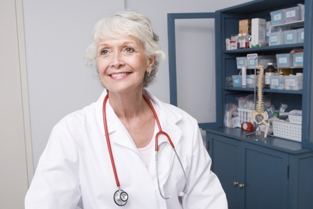 Senior medical practitioner stands at medical cabinet Stock Photo - 12738033