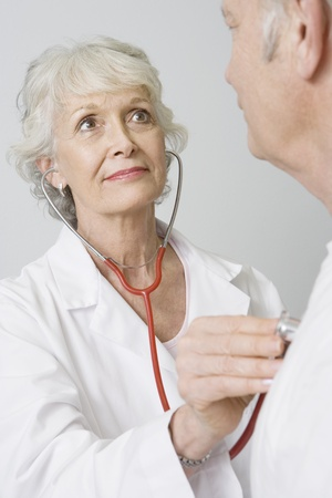 Senior medical practitioner examines man with stethoscope Stock Photo - 12738036