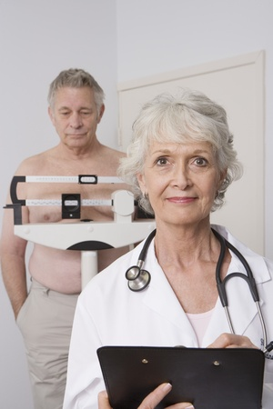 Senior medical practitioner stands with clip-board Stock Photo - 12738042